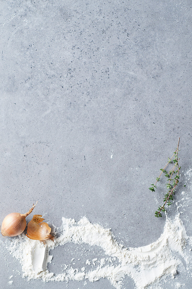 A grey surface with an onion, flour and thyme
