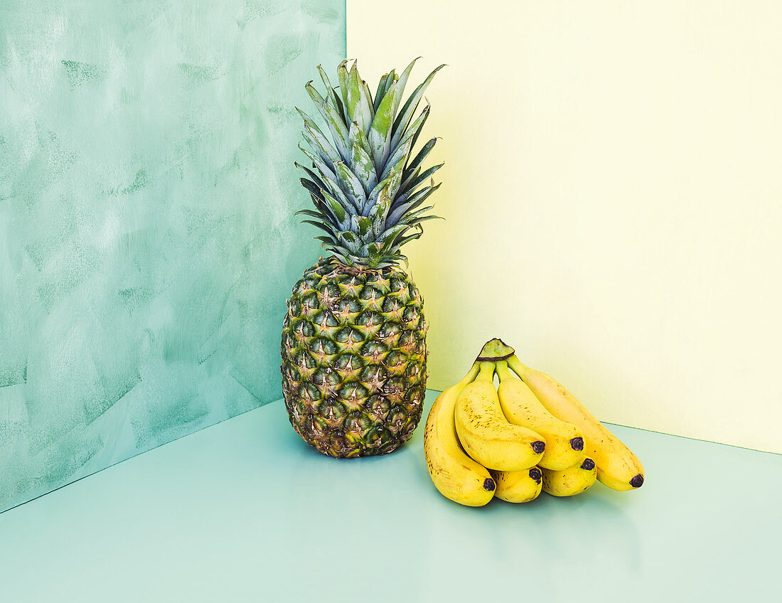 Whole ananas and bunch of bananas over yellow and green background