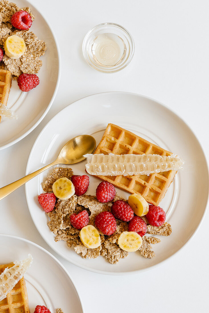 Whole graine cereal with fresh raspberries and banana, waffles and honeycombs