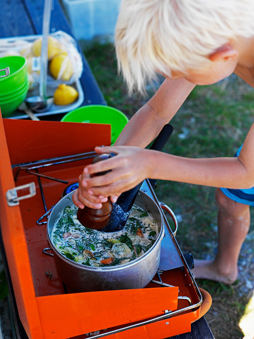 A boy seasoning crab soup with ground pepper on a camping stove