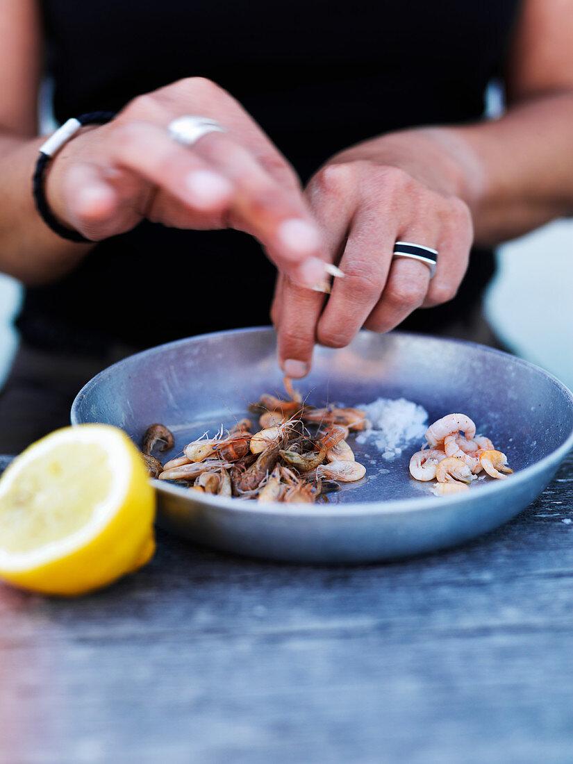 A woman peeling shrimps