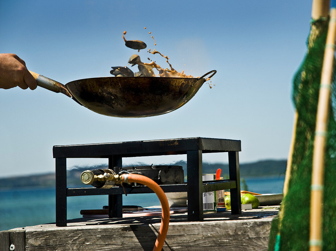 Food being tossed in a wok over a gas cooker on a beach