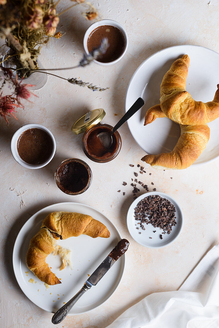 Breakfast with croissants, cocoa, hazelnut spread and cocoa nibs