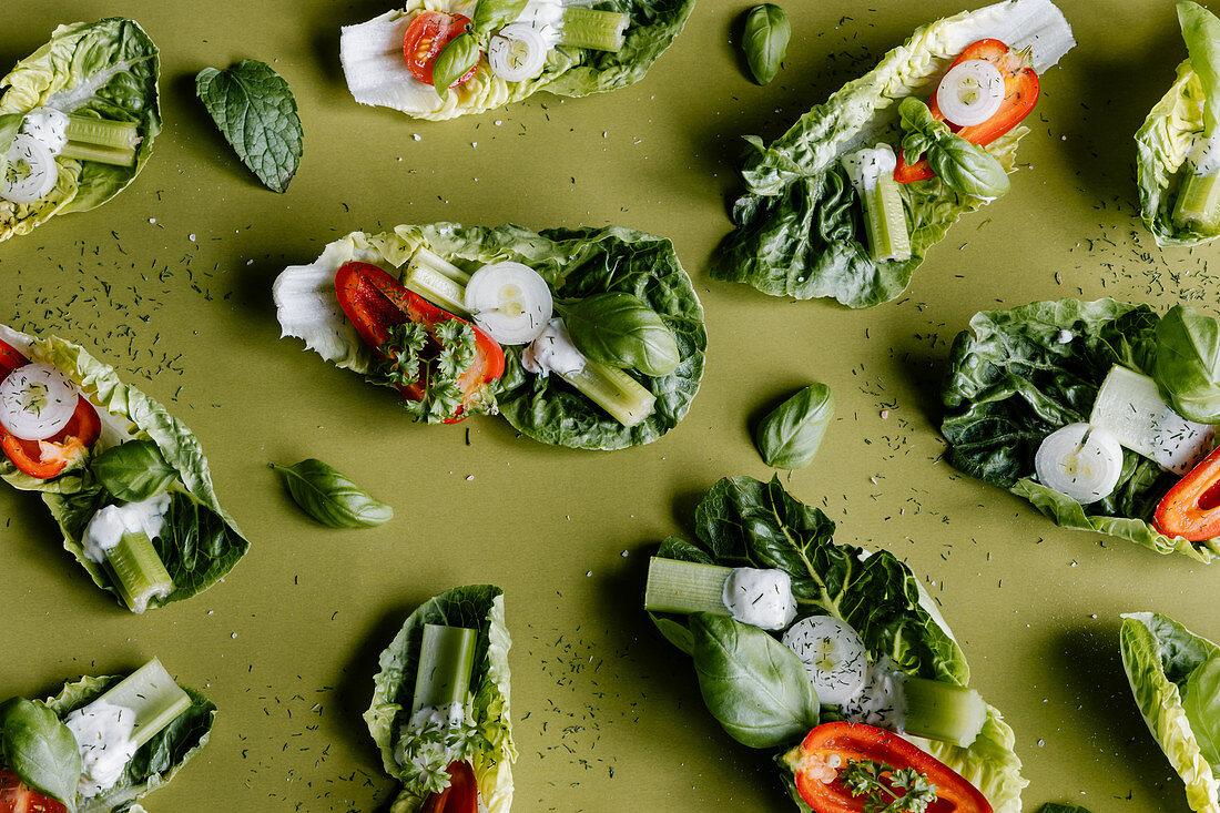Romaine lettuce salad bitesize snacks with cherry tomatoes, paprika, celery, onion and greek yogurt dressing