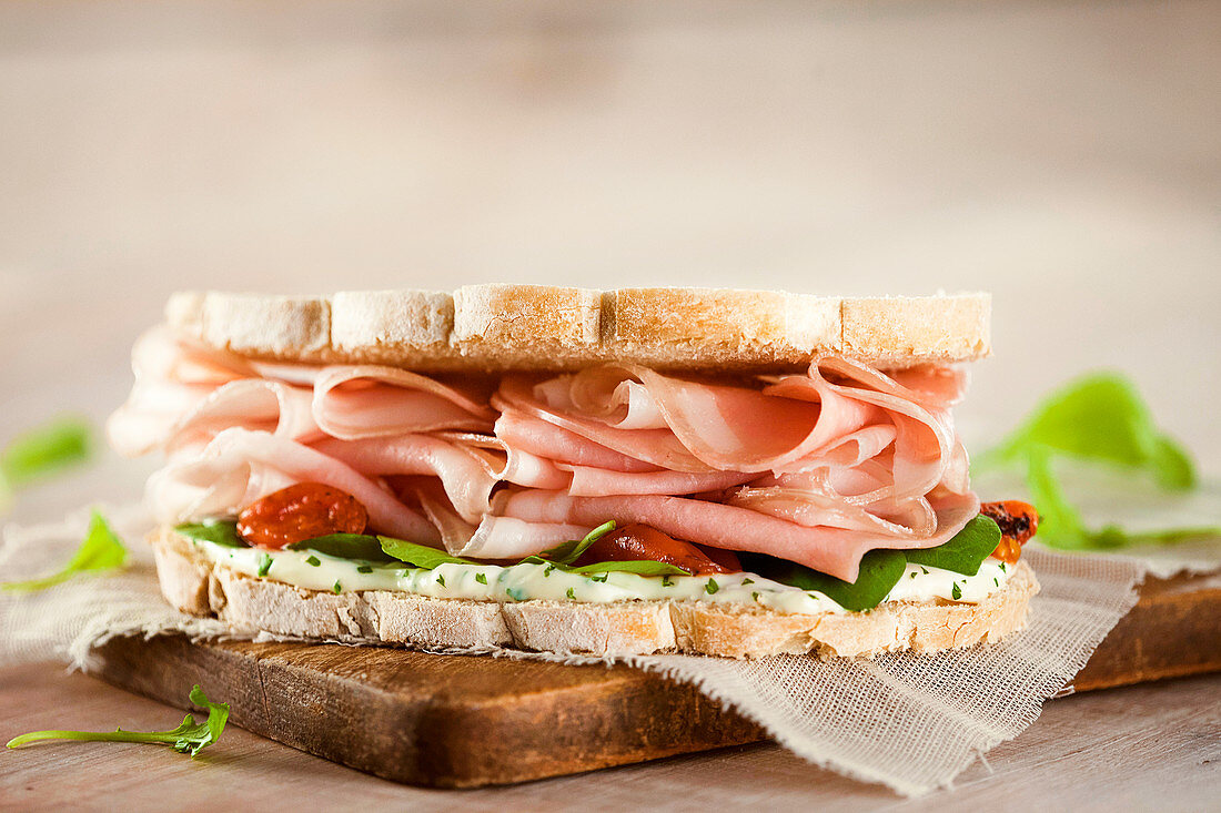 Ham sandwich on white bread, with tomato, arugula and creamy cheese dressing.