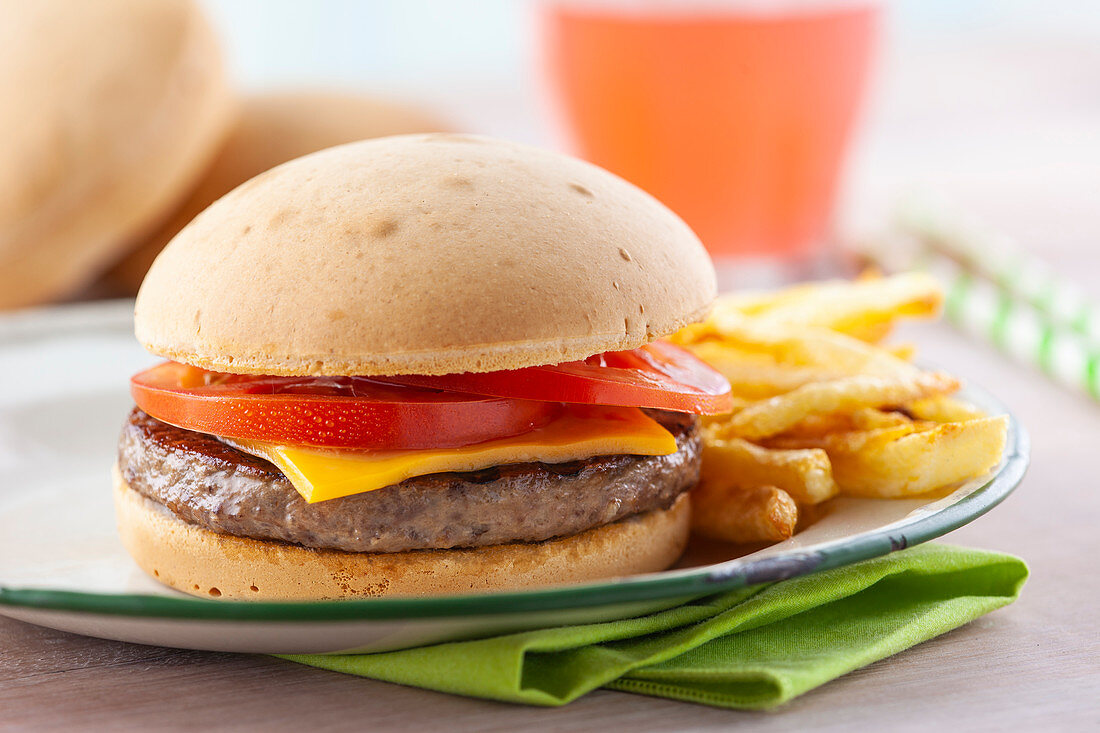 Burger sandwich with tomato and cheddar on white plate with fried potatoes