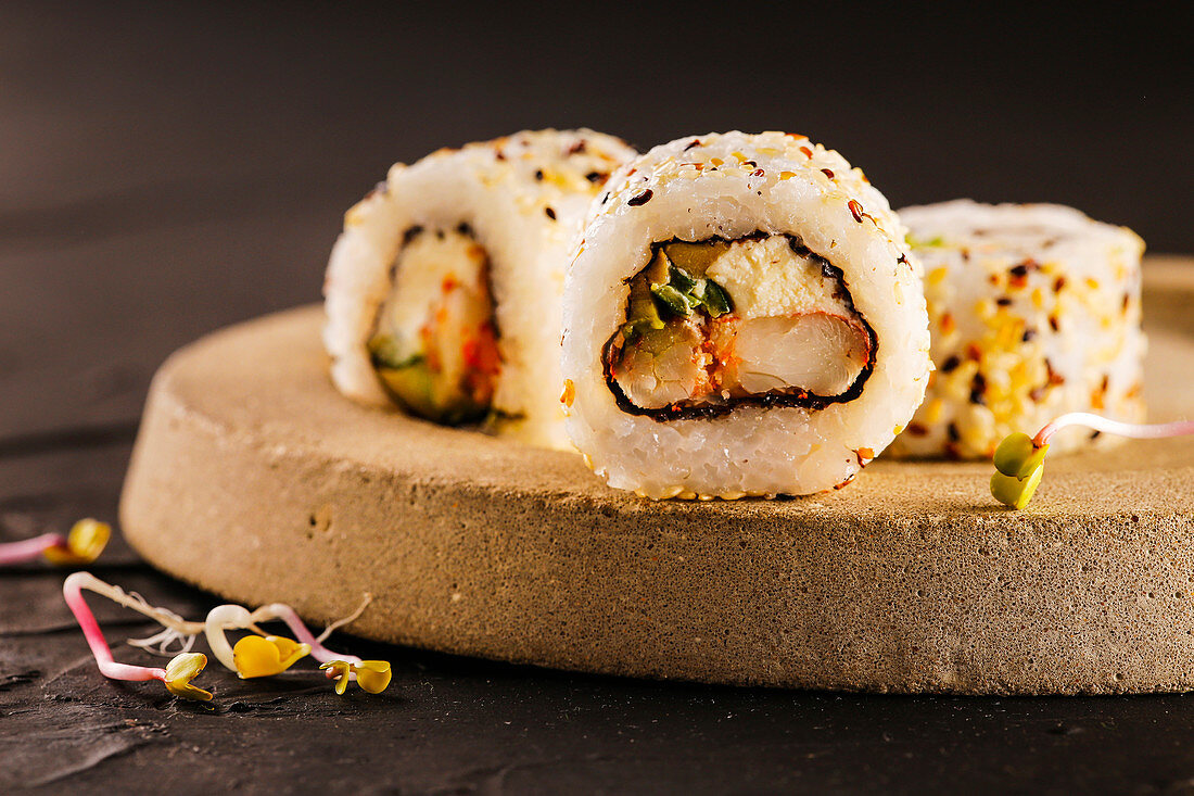 Sushi rolls filled with shrimp and cream cheese, covered with sesame seeds.
