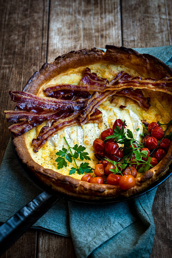 Two cheese 'Dutch Baby' with camembert, bacon and tomatoes