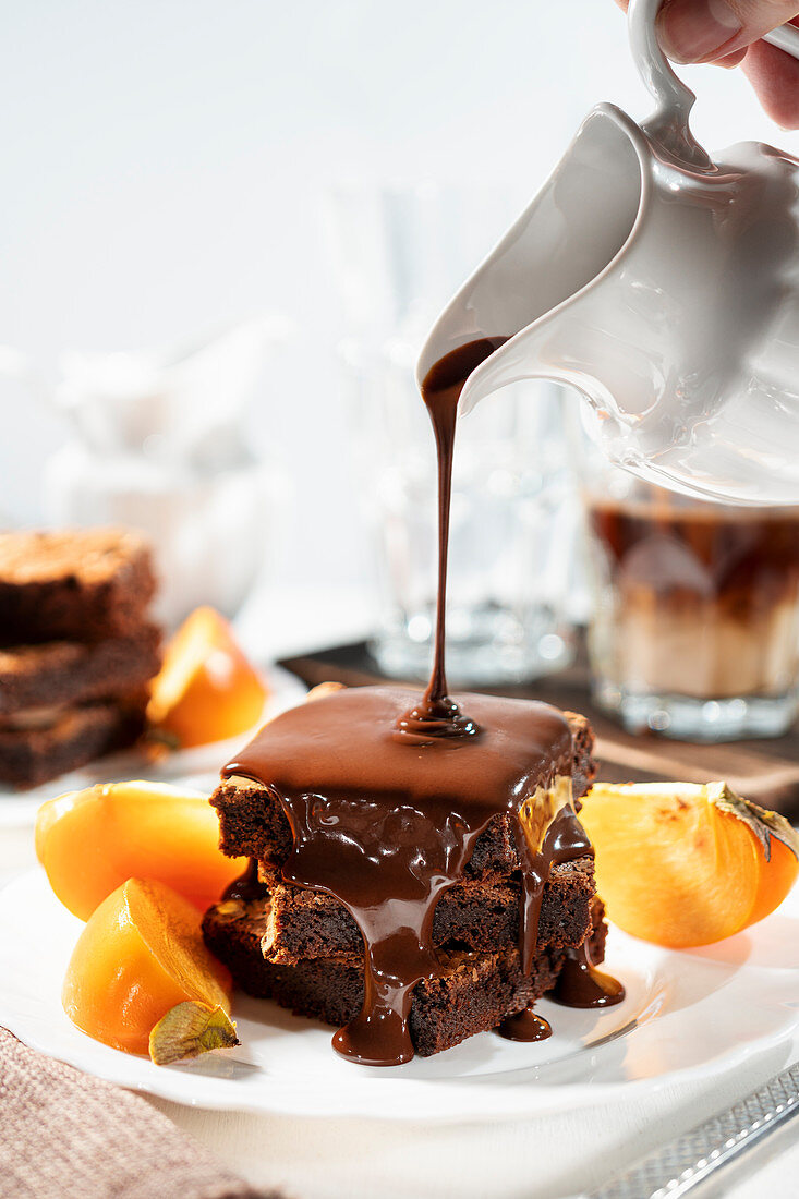 Chocolate sauce being poured over gluten-free brownies