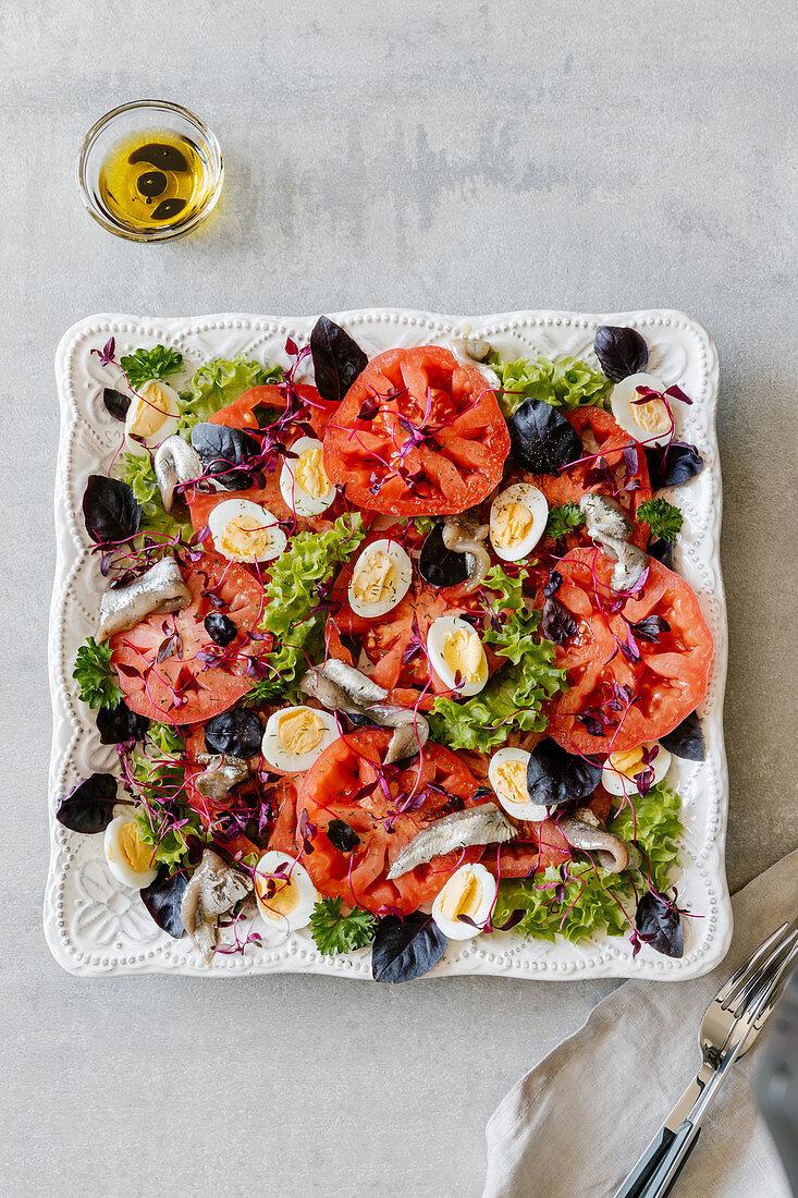 Salad made with anchovies, quaileggs, tomatoes, amarantus, lettuce and purple basil