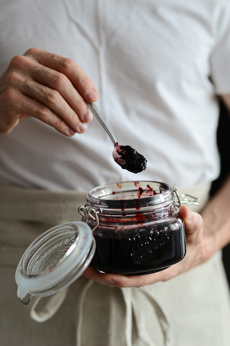 Man is holding a jar of blueberry jam in his hands