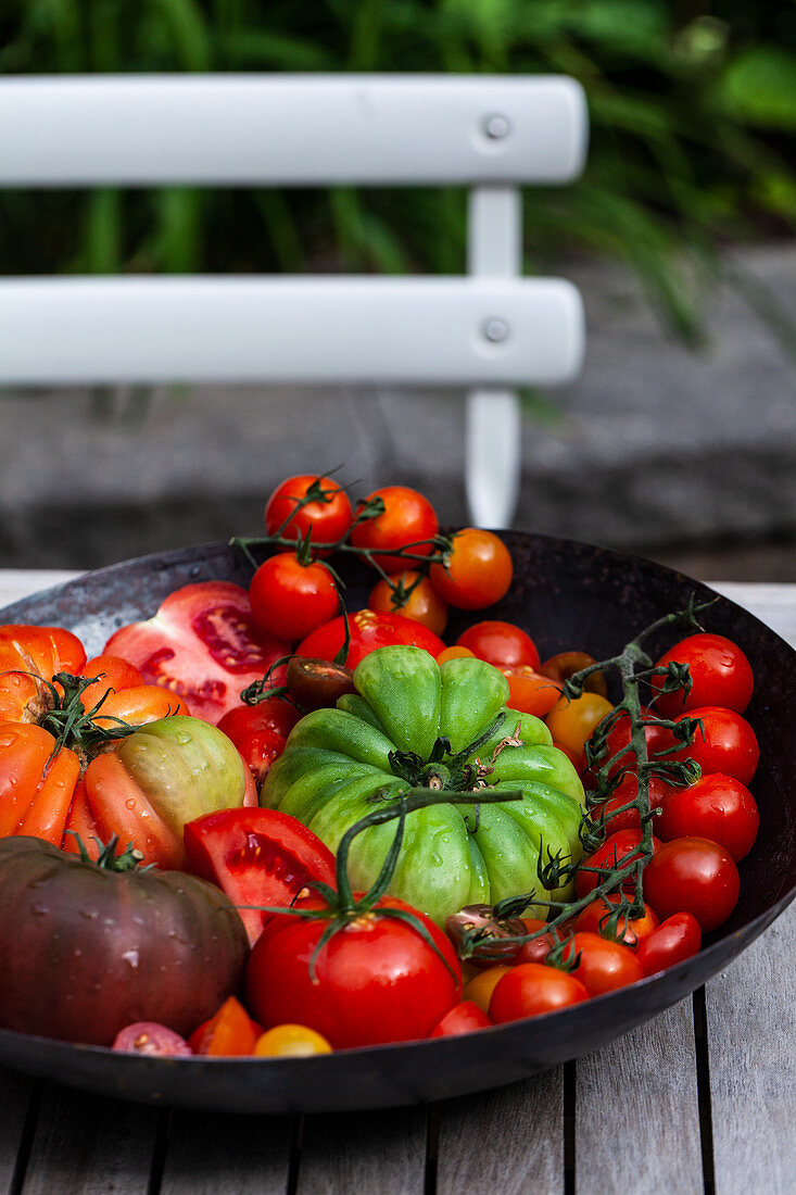 Various types of tomatoes - outdoor table and chair, with an antique colander