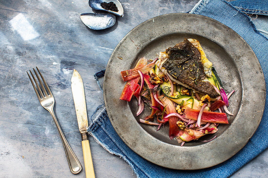 Fried fish fillet on a vegetable salad with rhubarb