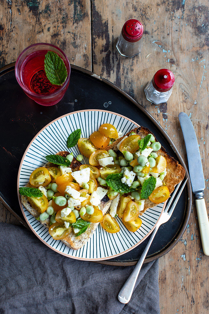 Crostini with yellow tomatoes, peas, mint and feta cheese