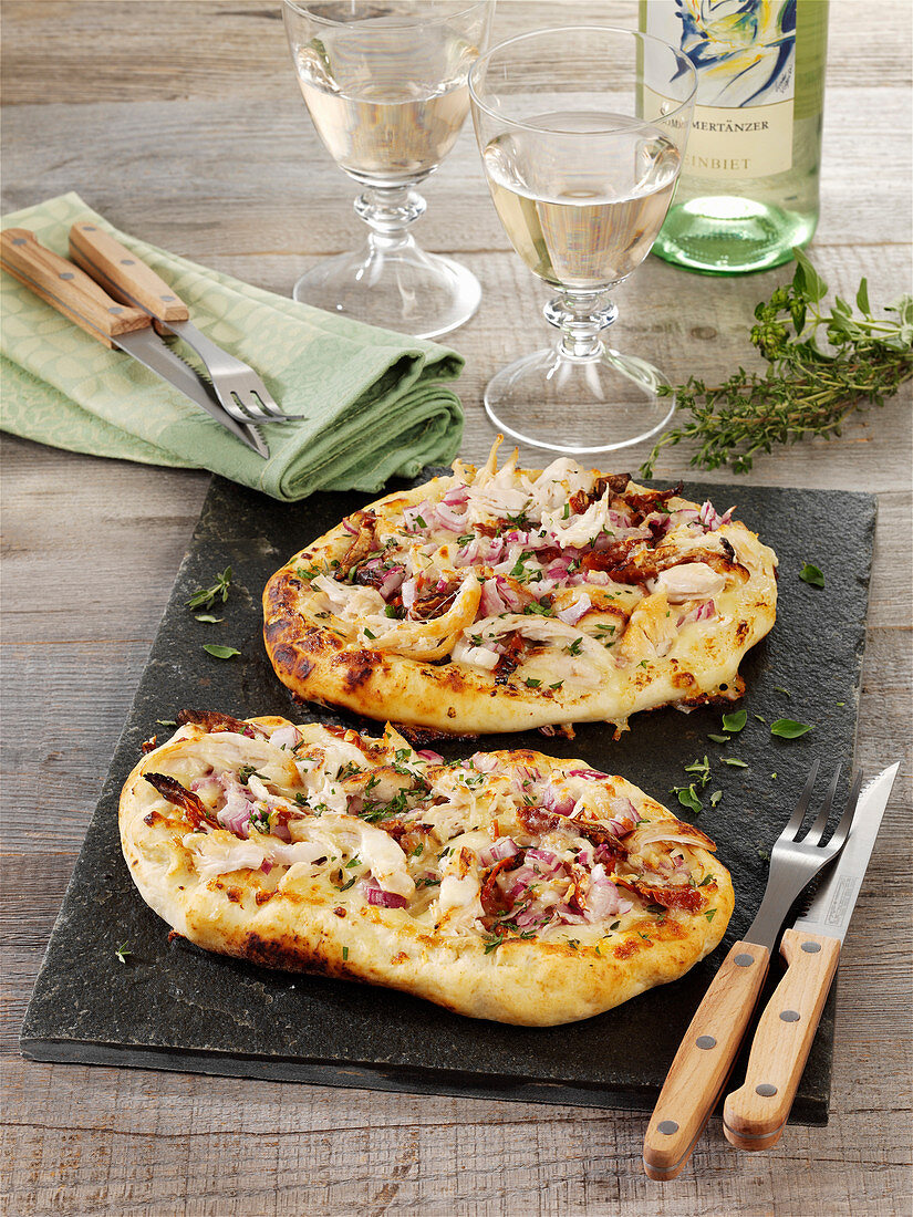 Chicken pizza with dried tomatoes, onions and mozzarella