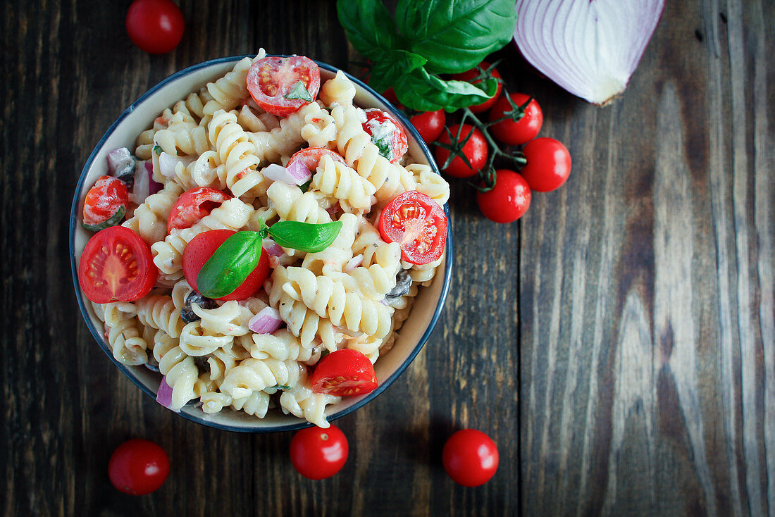 Pasta salad with basil, tomatoes, black olives, red onion and feta cheese