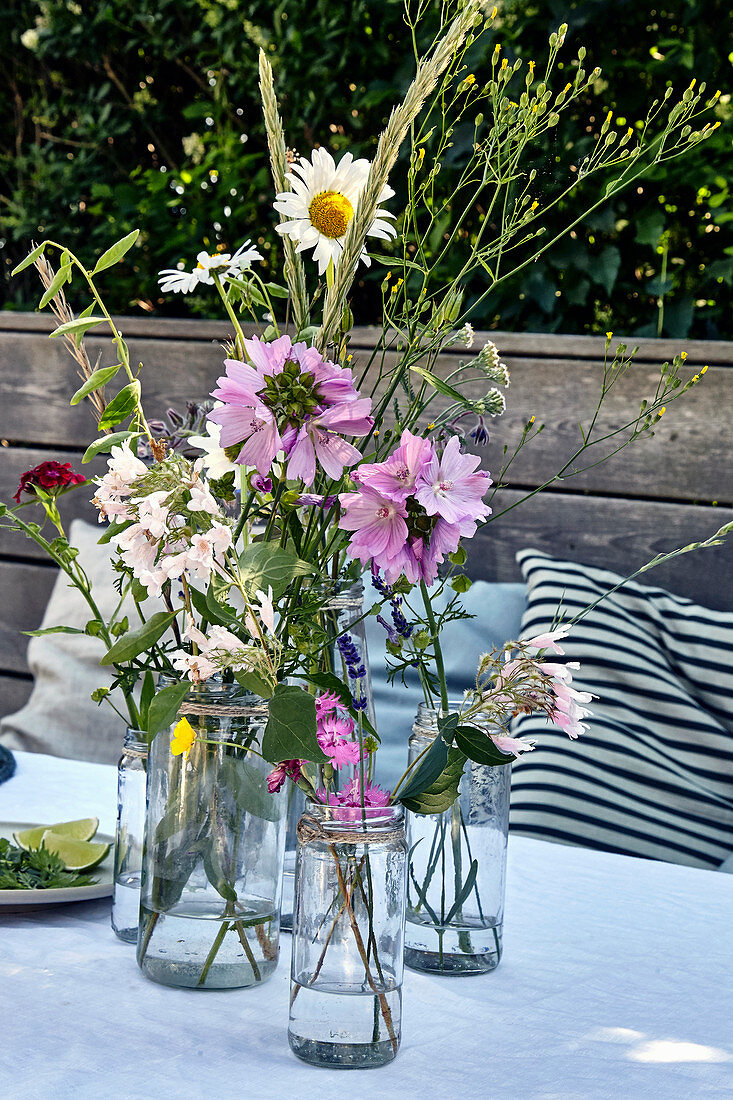 Meadow flowers in water glasses as a summer table decoration