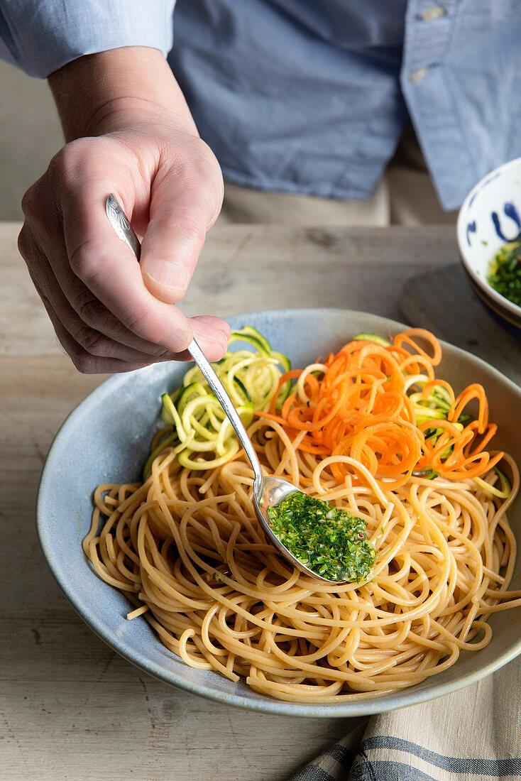 Pour pesto over wholemeal spaghetti with vegetable spirelli