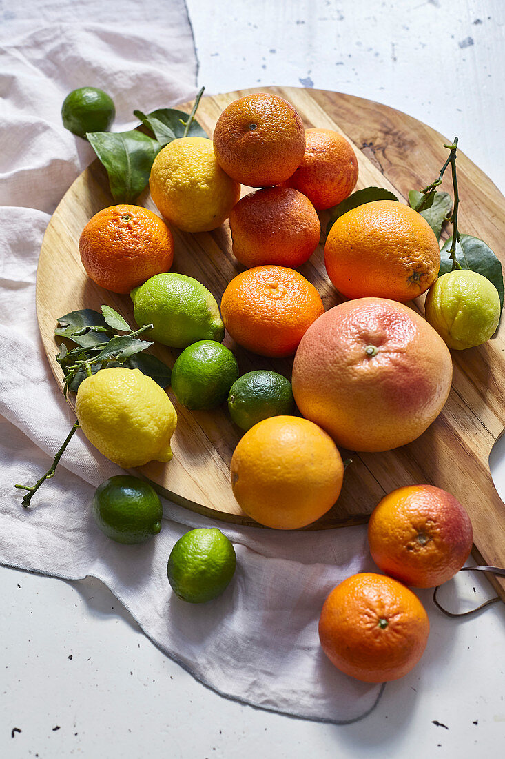 Various citrus fruits on a wooden board
