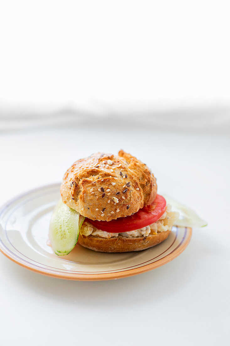 Bun with russian salad, tomato and cucumber