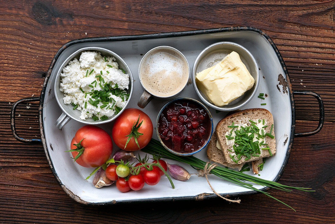 Rustic breakfast made from organic ingredients with coffee, butter, bread, cream cheese and tomatoes