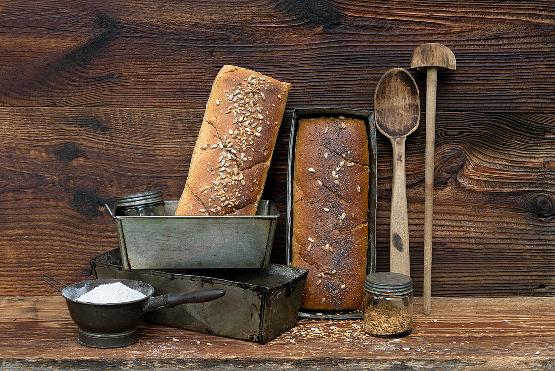 Homemade bread with vintage kitchen utensils in front of a wooden background