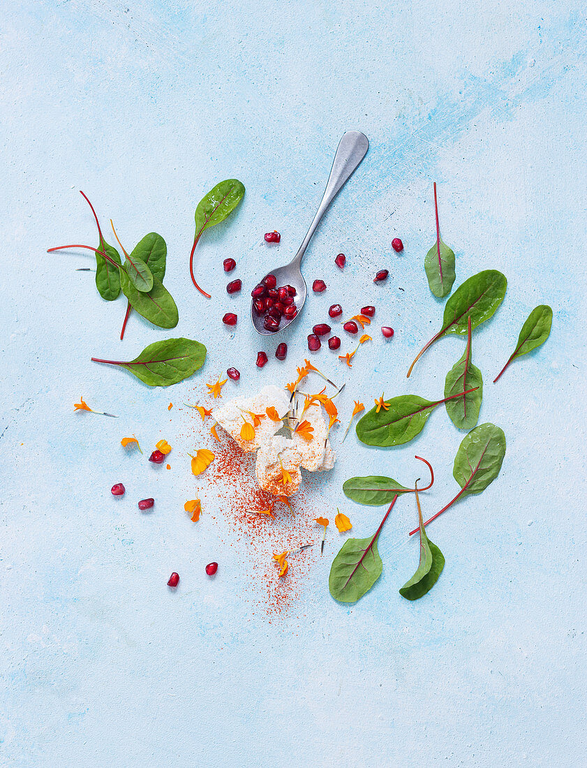 Feta cheese, flower petals, pomegranate seeds and sorrel leaves