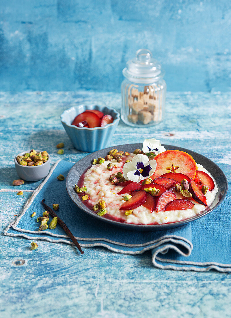 Breakfast risotto with plums, apples and pistachio nuts