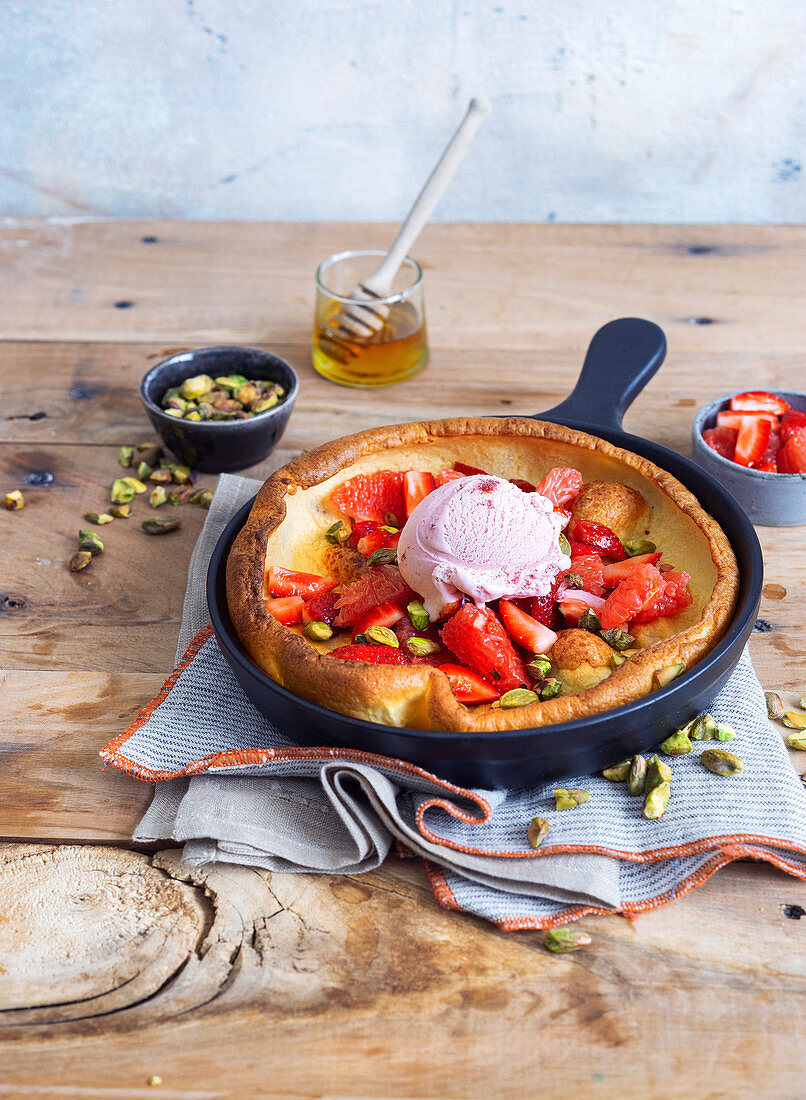 Dutch Baby with strawberry and grapefruit salad, strawberry ice cream and pistachio nuts