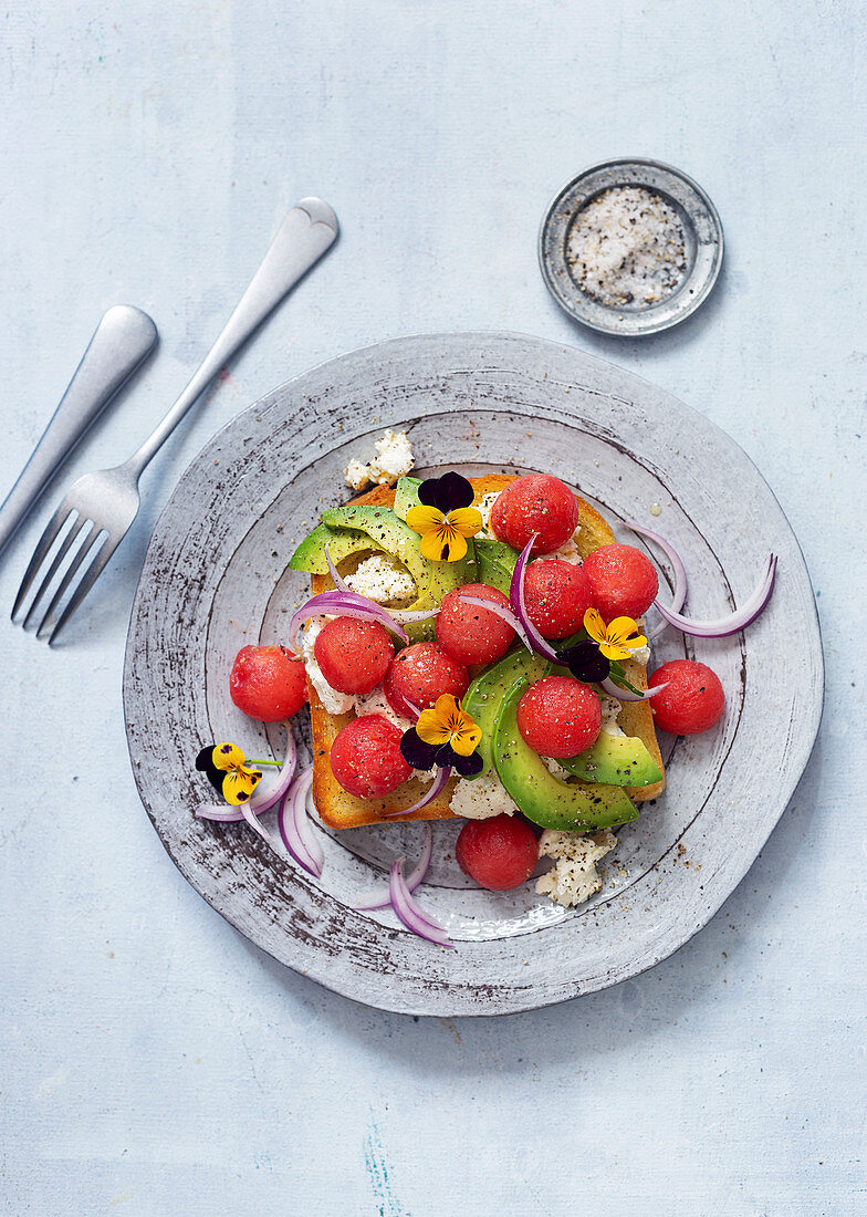 Toast with melon, ricotta, avocado and edible flowers