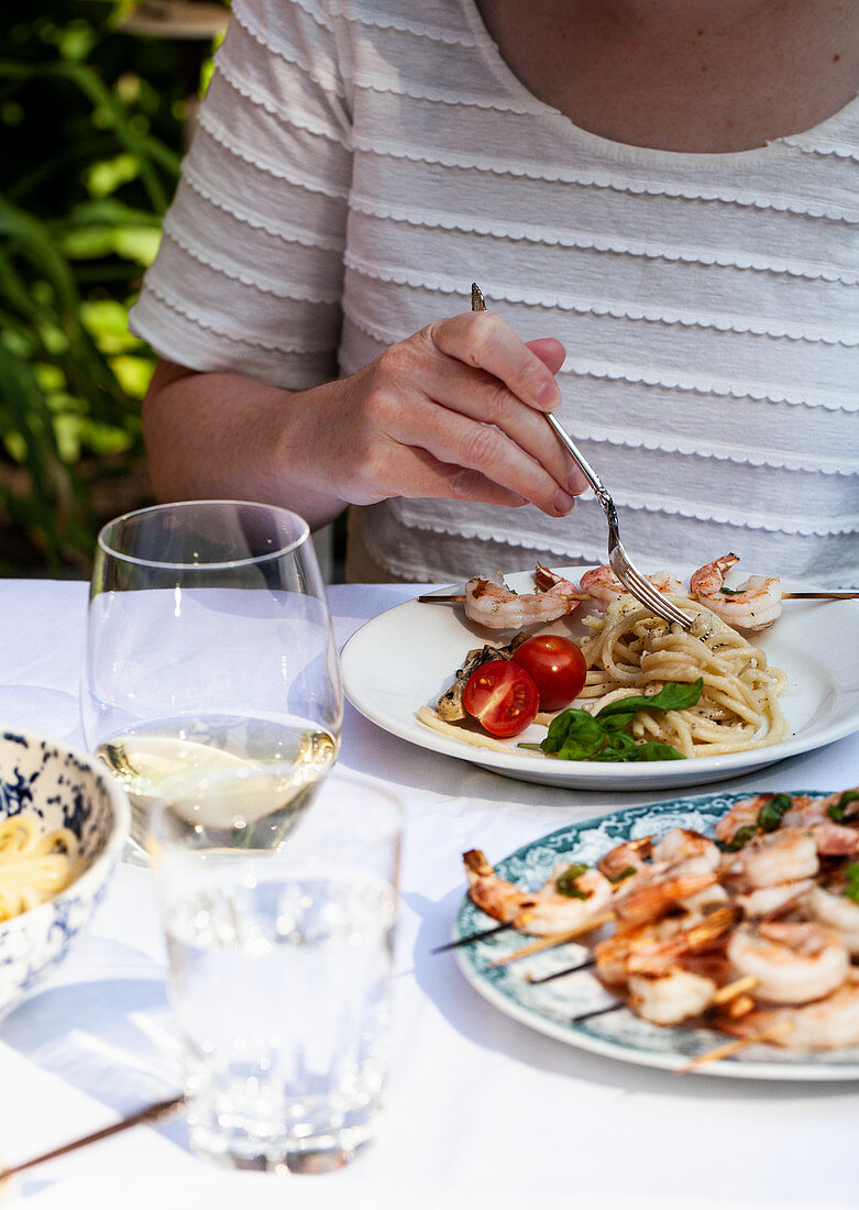 Woman twirling pasta cacio e pepe on a plate with shrimp skewers, tomatoes and white wine at an outdoor table