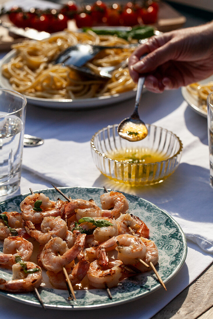 Shrimp skewers with basil butter sauce, pasta cacio e pepe (pasta with cheese and pepper) and tomatoes on an outdoor table