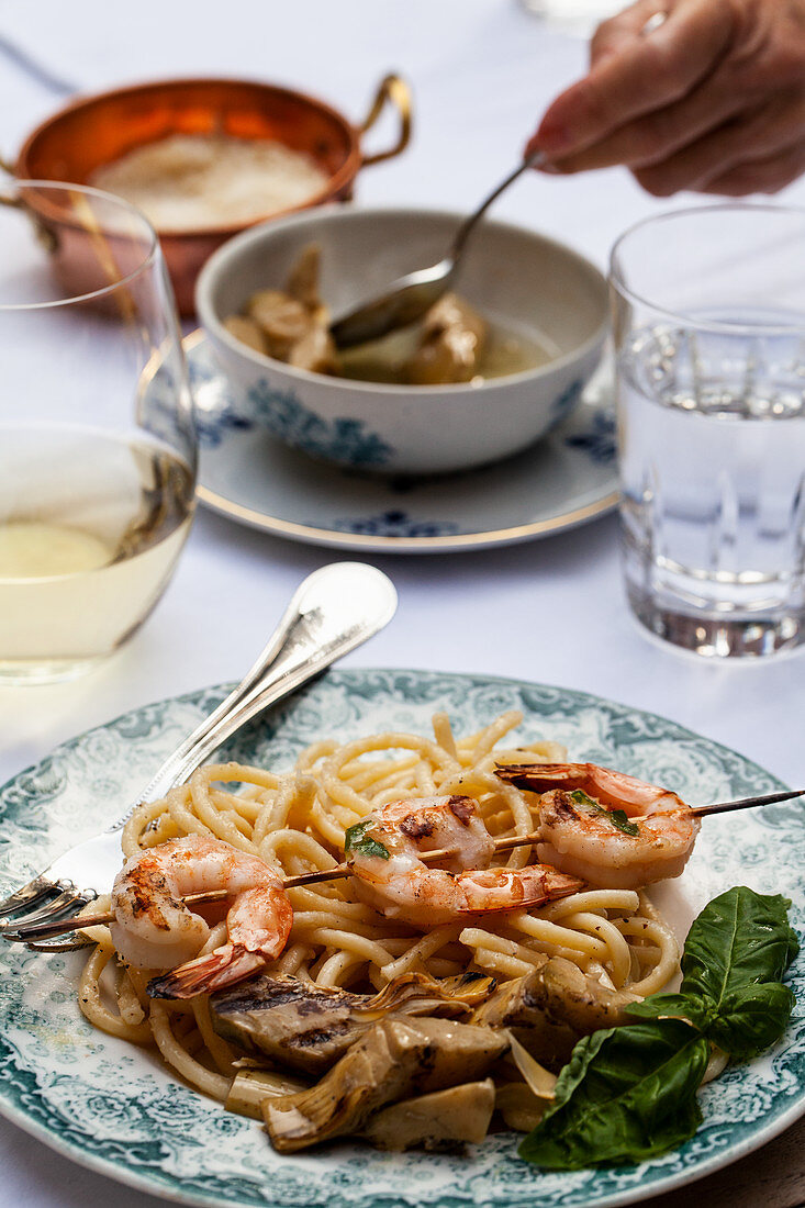 An outdoor table with pasta cacio e pepe (pasta with cheese and pepper), shrimp skewers with basil, artichokes and white wine