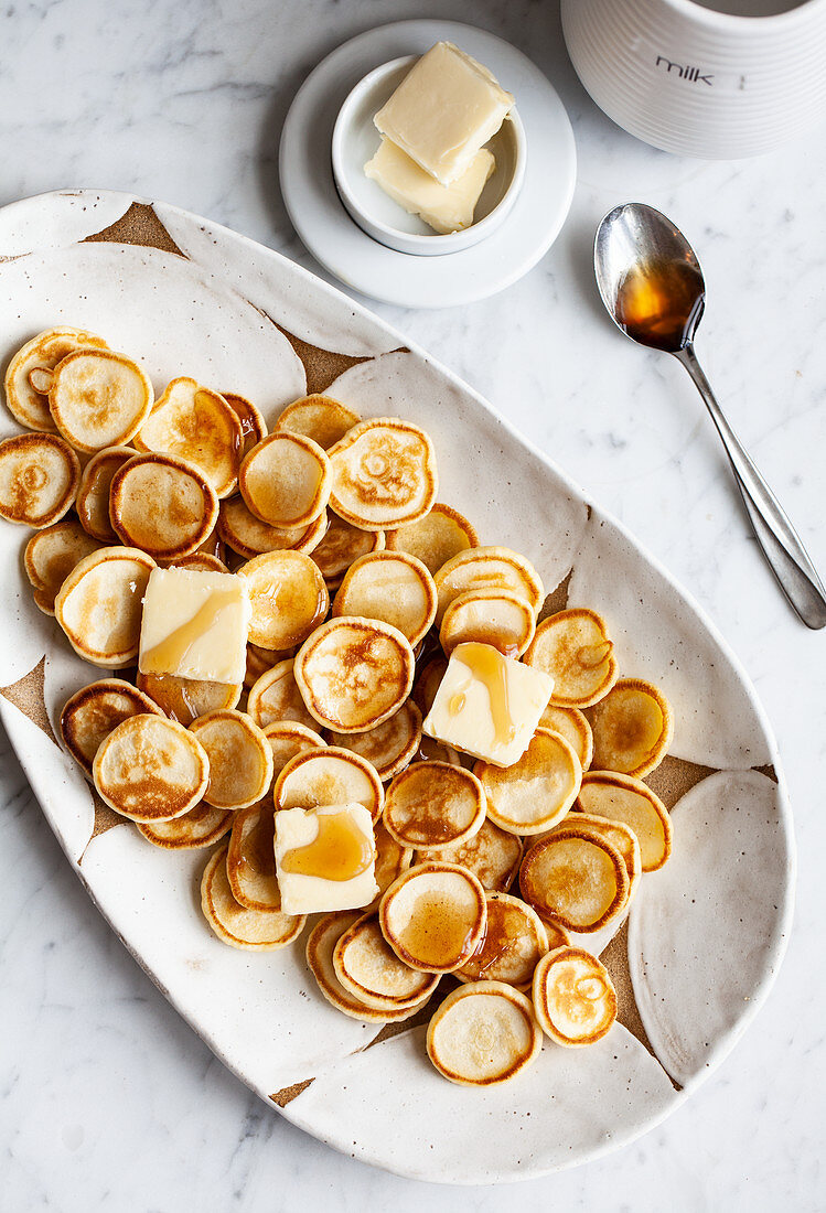 A platter of mini pancakes with butter and a jar of maple syrup
