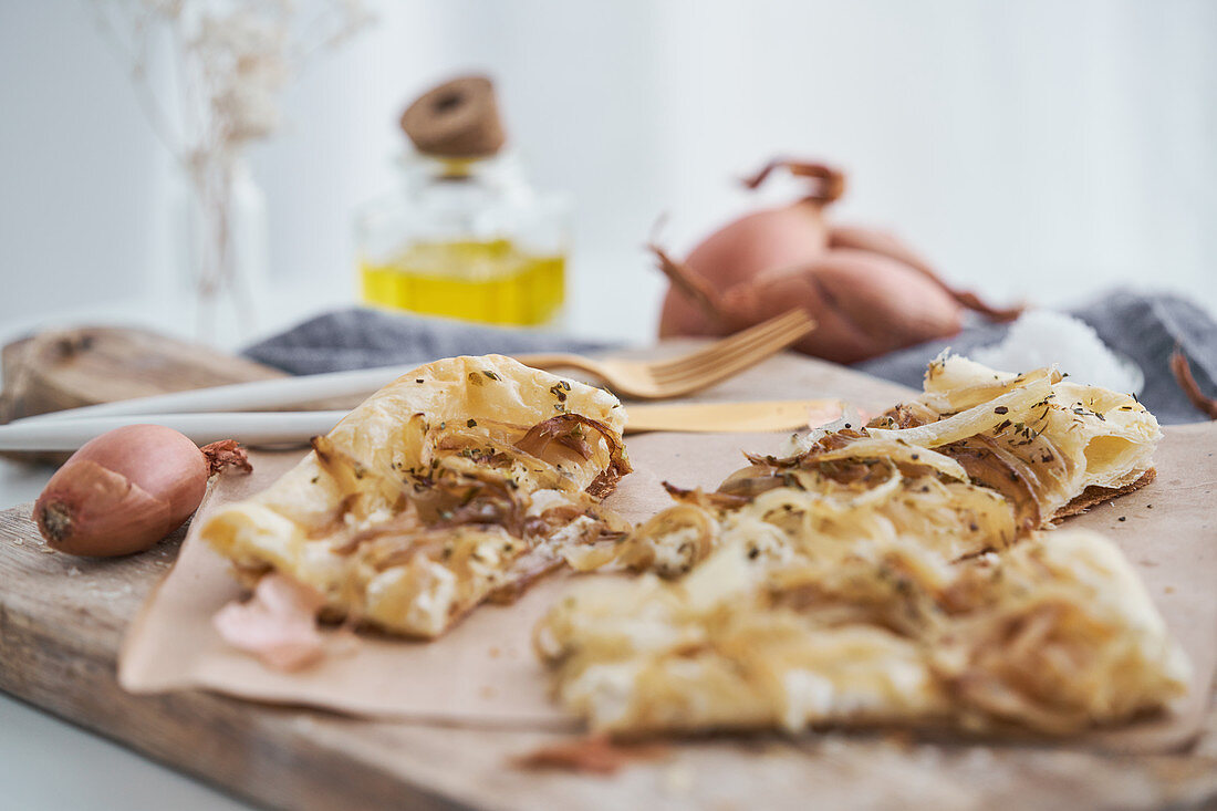 Puff pastry with onion and cream cheese placed on rustic cutting board