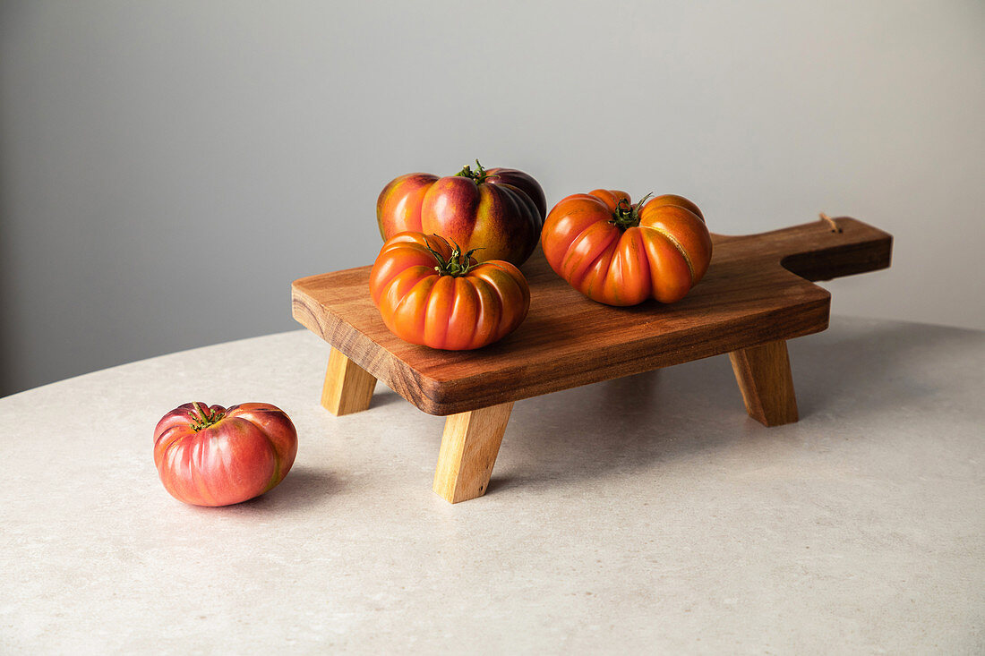 Composition with raw red tomatoes arranged on wooden board on marble table