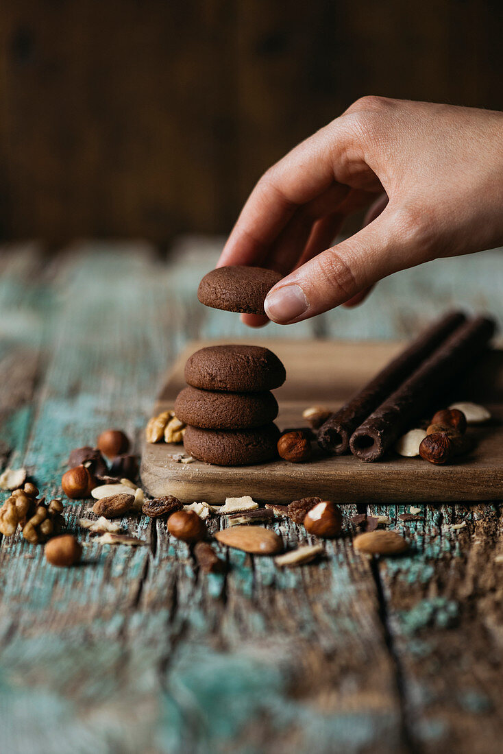 Hands taking a chocolate cookie with nuts