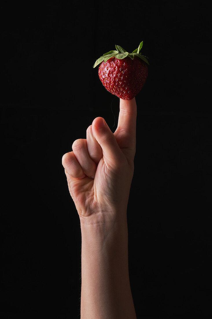 Kinderhand spielt mit Erdbeere