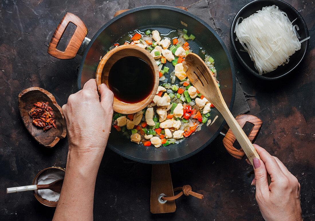 Sojasauce zu Reisnudeln mit Paprika und Hühnerfilet geben