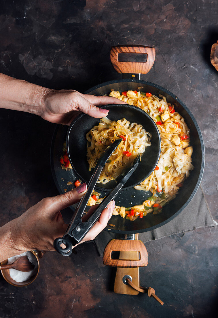 Crop female with kitchen tongs putting delicious homemade stir fry chicken noodles from pan into bowl