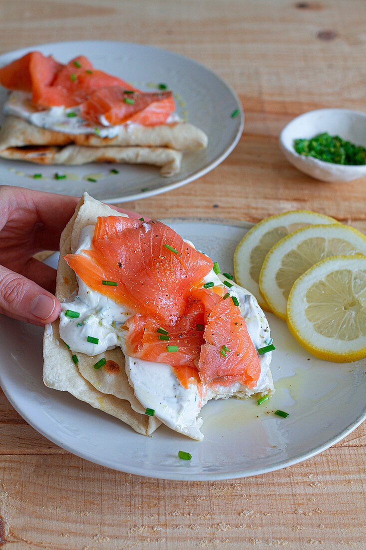 Flatbread with sour cream and salmon slice garnished with green onion and lemon