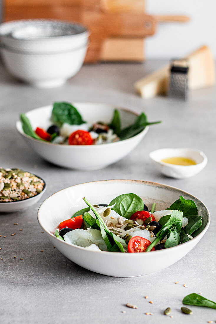 Bowls with delicious salad made with fish, green spinach, chopped cherry tomatoes and black olives, garnished with seeds