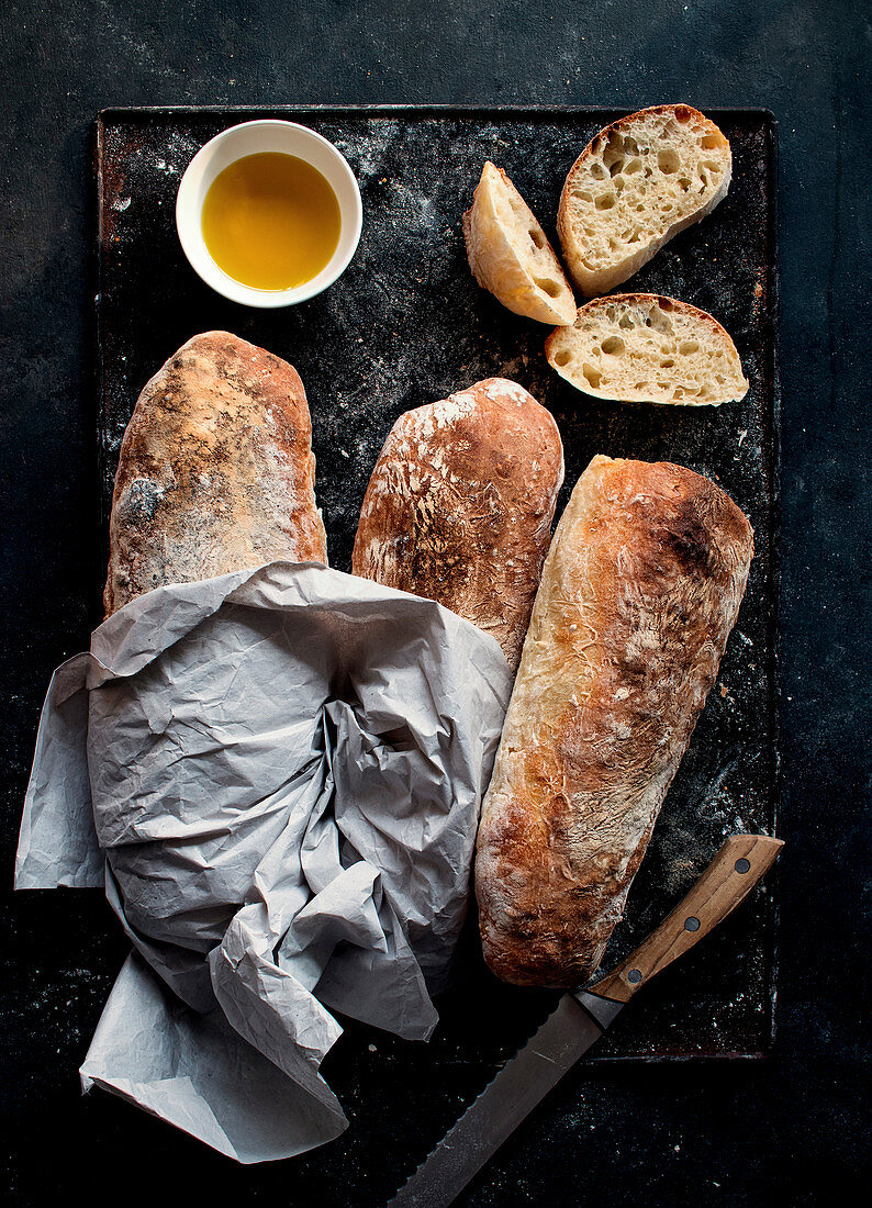 Ciabatta bread on rustic board, olive oil and knife with bread slices on dark background