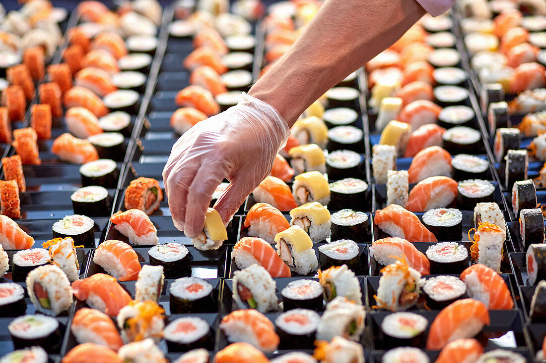 Anonymous salesman in protective gloves putting in sushi in plastic container on market