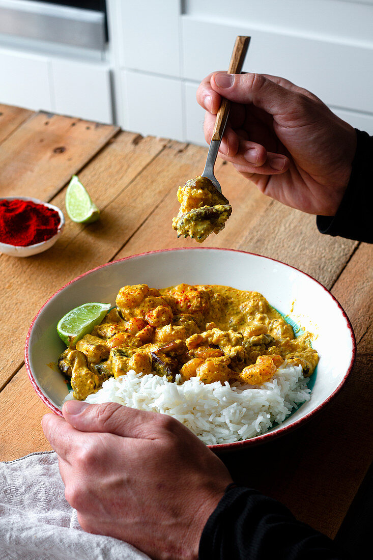 Taking piece of spicy curry made of prawns and mushrooms and served with rice and lime slices