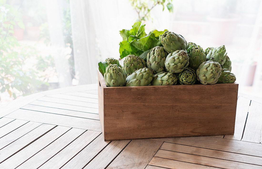 Artischocken und Salat in Holzkiste