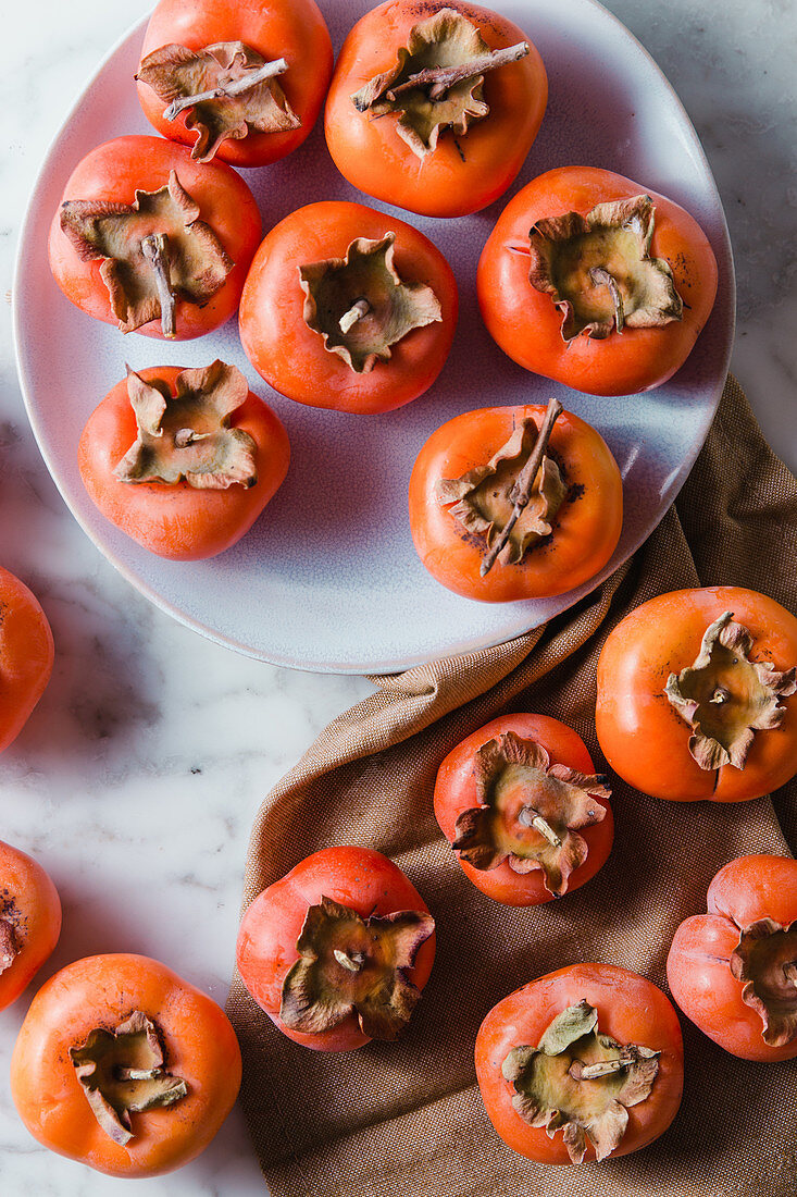 Top view of pile of fresh persimmons on plate placed on white table