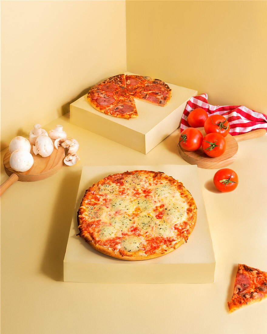 Fresh mushrooms and tomatoes placed near delicious pizzas and checkered napkin in beige corner