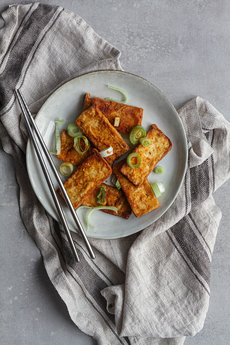 Top view of tofu slices with fragrant pieces of garlic marinating in soy sauce