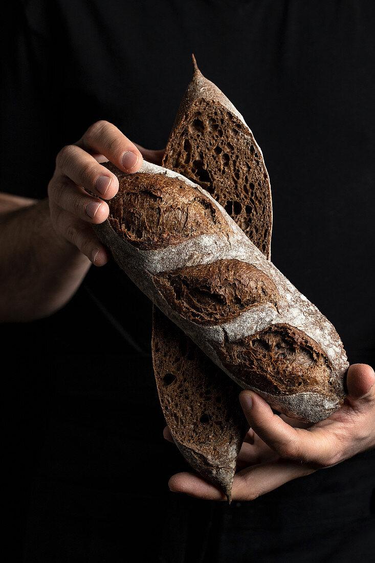 Crop male baker in apron holding cut in half loaf of fresh healthy artisan bread